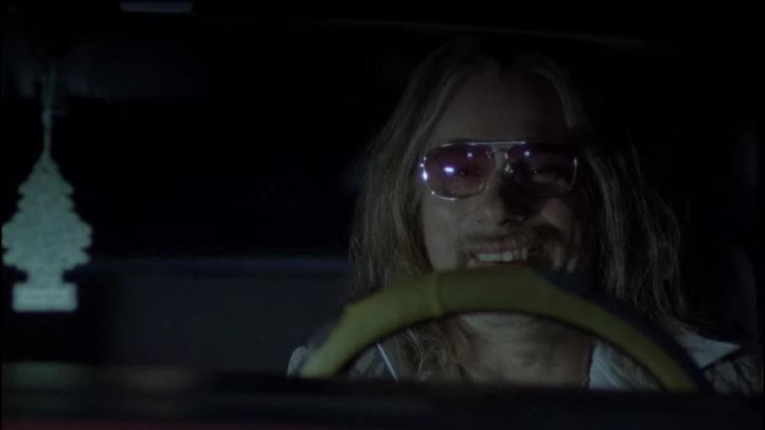 Im Film wird der Zuhälter Ulli vorgestellt, der im Auto sitzt. Er hat lange Haare und ein dreckiges Grinsen.
