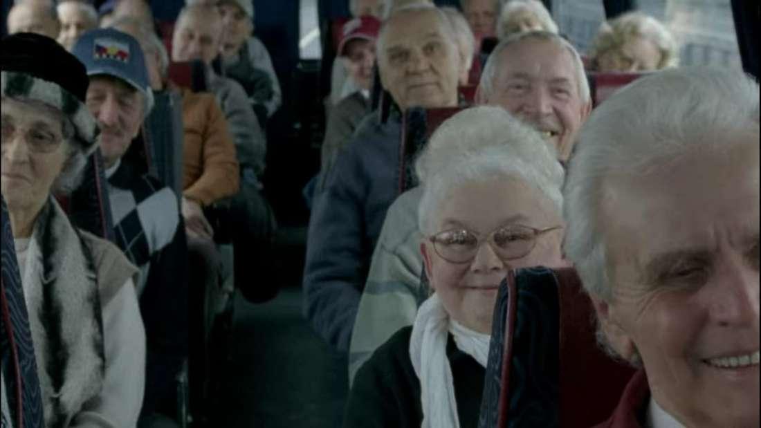 Im Film ist ein Reisebus voller Senioren zu sehen, die gespannt Hilmar lauschen.