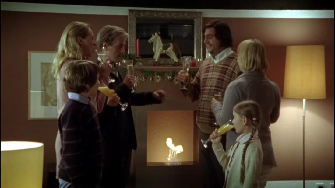 Hilmar und Tilmann sind gemeinsam mit deren Familien bei Tilmann Zuhause und feiern in einem geschmückten Wohnzimmer Weihnachten. Sie stoßen mit Getränken an.