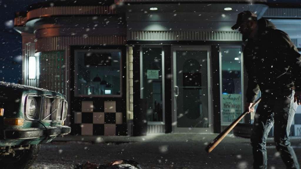 Zwei Männer stehen im Schnee vor einem Auto. Einer von ihnen hält einen Baseball-Schläger in der Hand.
