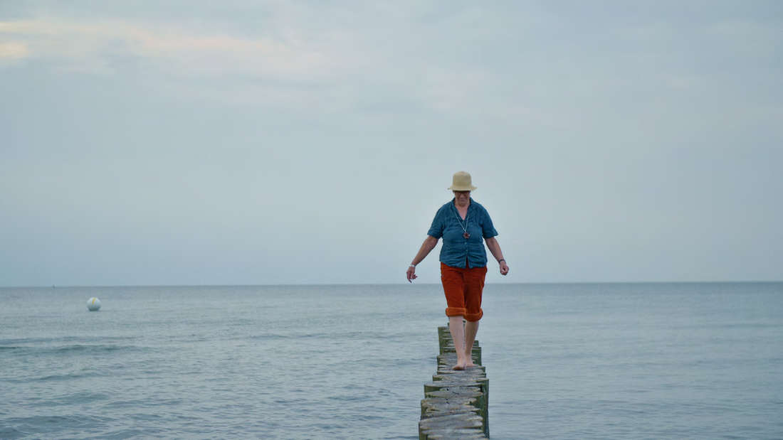 Eine Frau aus dem Film balanciert auf einem Steg im Wasser.