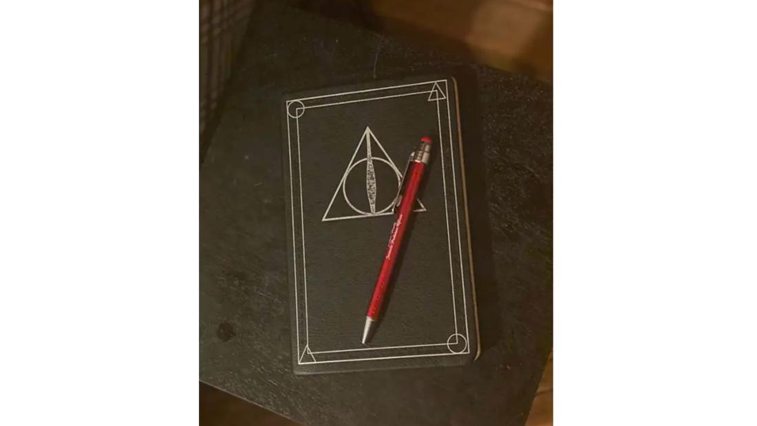 Eon Foto von einem Notizbuch mit dem Logo der Heiligtümer des Todes auf einem Tisch