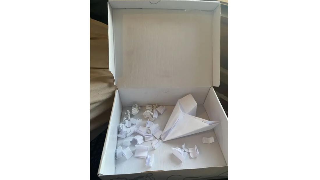 Box, in der viel zusammengefaltetes Papier und ein Papierflugzeug liegt