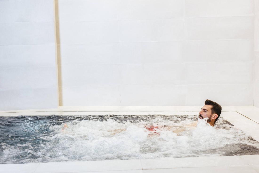 Ein Mann mit Bart, der in einem Whirlpool sitzt