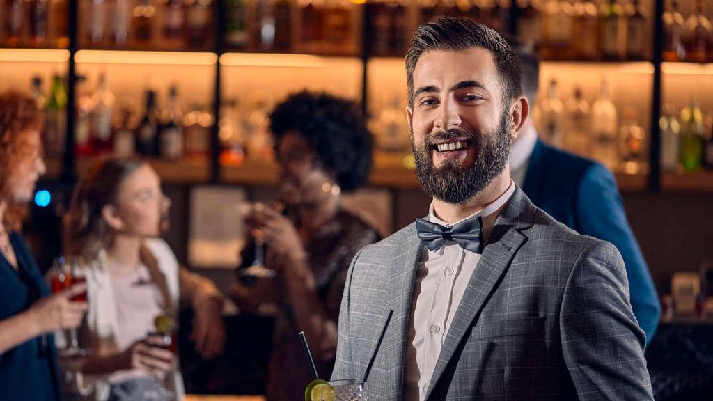 Ein lächelnder Mann mit Bart und einem Drink in einer Bar