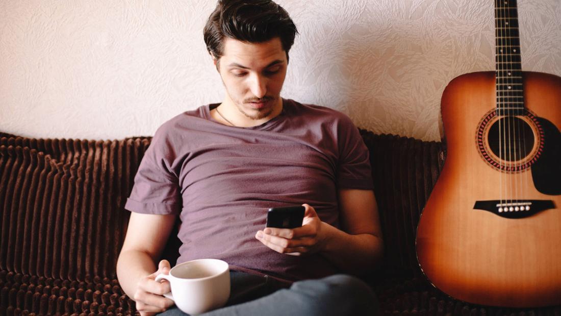 Mann der auf dem Sofa sitzt und geschockt auf sein Handy starrt