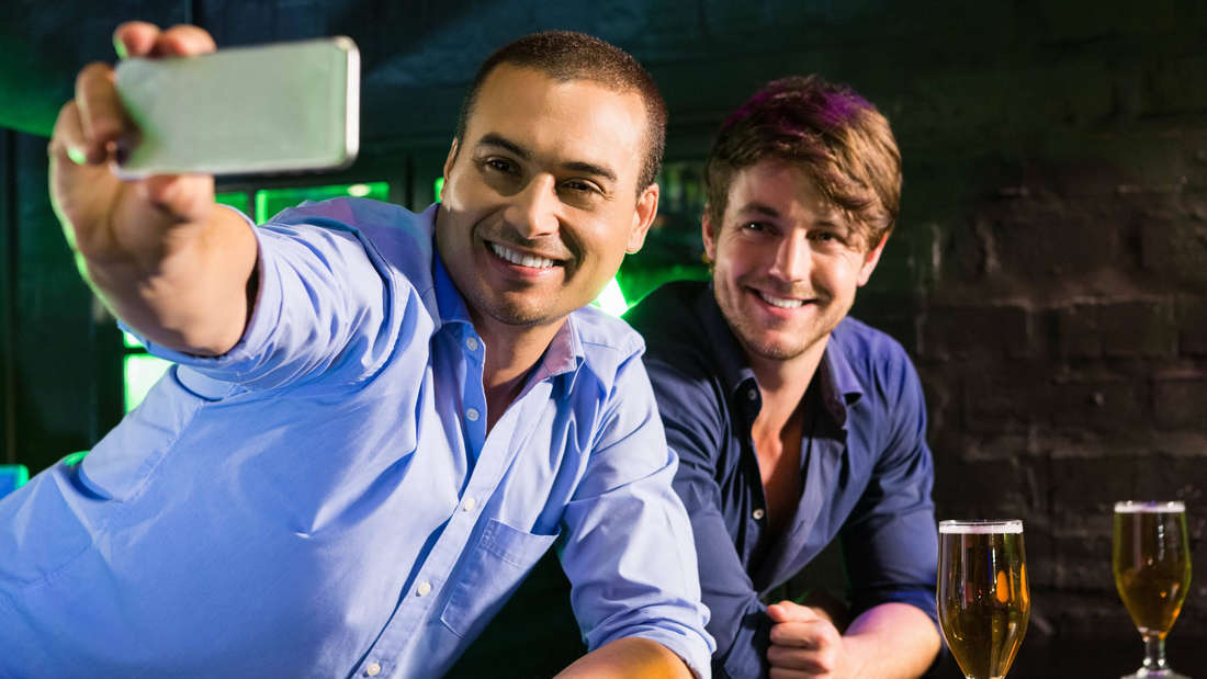 Zwei Männer nehmen zusammen in einer Bar ein Selfie auf