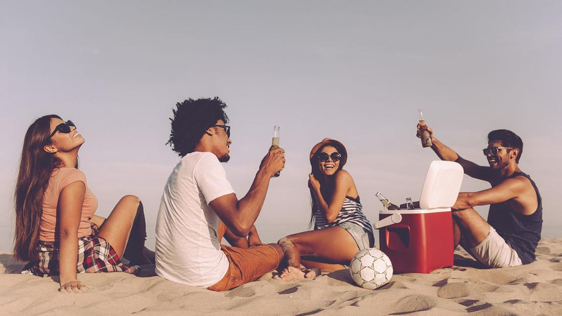 Mehrere Jugendliche feiern am Strand eine Party und haben Flaschen dabei