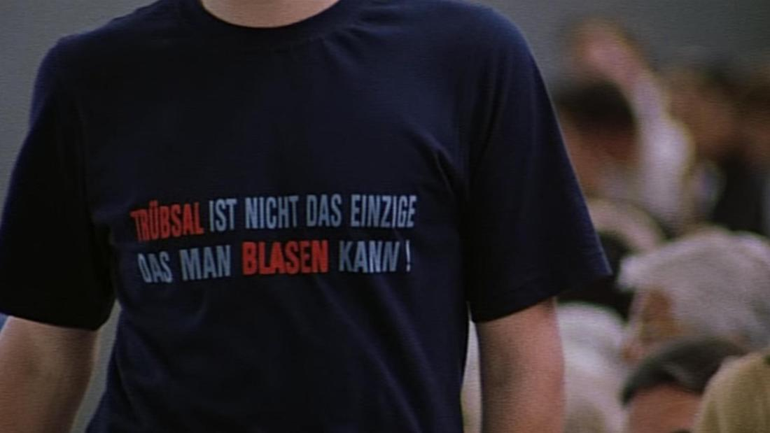 """Auf Tims Shirt steht: """"Trübsal ist nicht das einzige, was man blasen kann."""""""