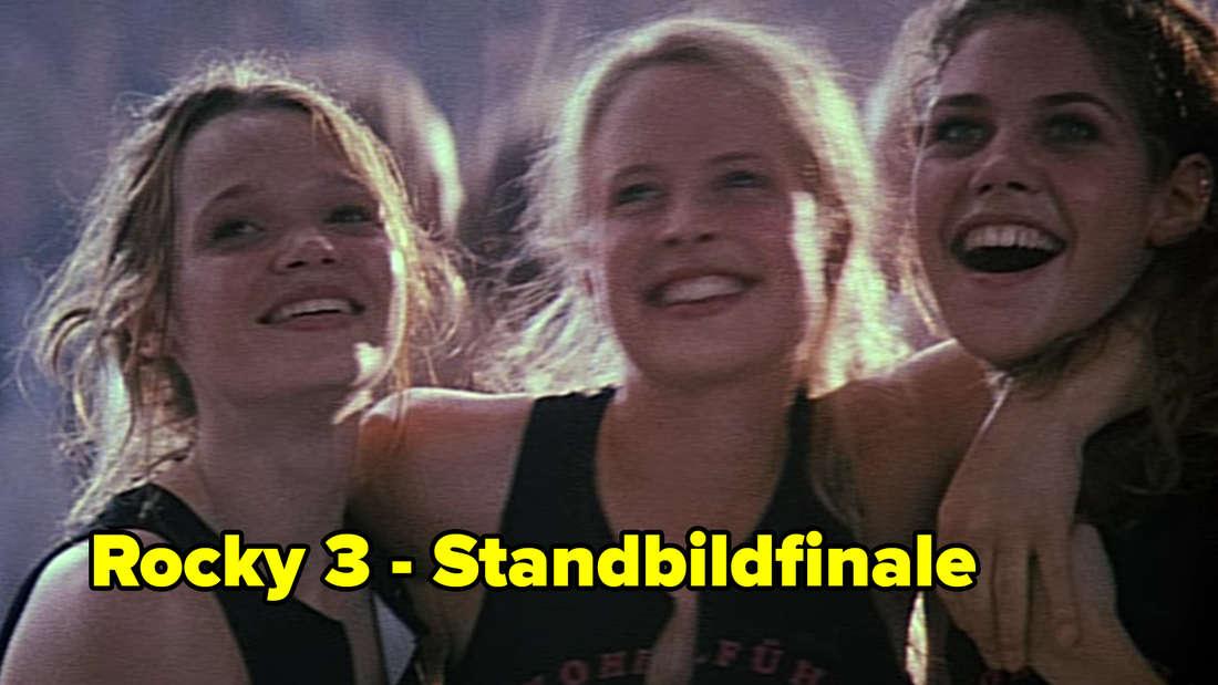 Inken, Lena und Vicky umarmen sich nach dem Spiel. Darunter steht: Rocky 3 - Standbildfinale.