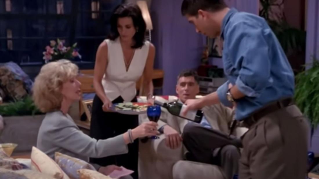 Eine Familie sitzt um einen Tisch und ein Mann schenkt einer älteren Frau ein Getränk ein