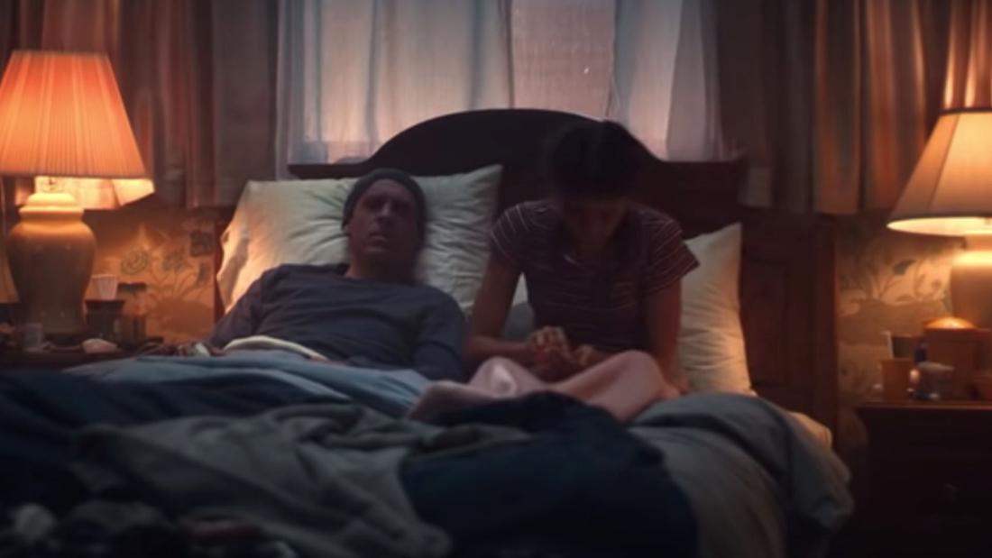 Ein Mann liegt im Bett und hält die hand einer Frau, die auf dem Bett sitzt. Der Mann sieht sehr kränklich und die Frau besorgt aus.