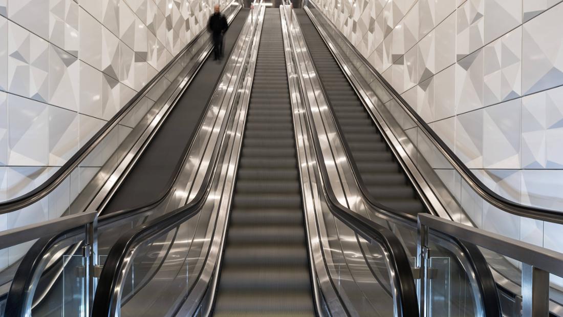 Ein Bild einer Rolltreppe, auf der verschwommen ein Mann zu sehen ist