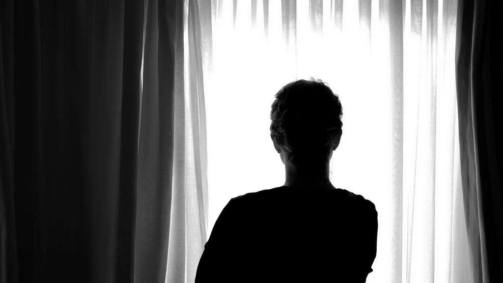 Eine junge Frau steht in einem Zimmer eines Frauenhauses in Niedersachsen, Nienburg.