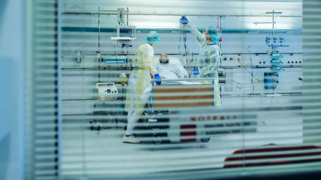 Eine Person, die im Krankenhaus liegt und von Ärzten versorgt wird.