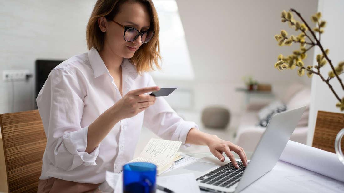 Eine Frau, die vor ihrem Laptop sitzt und auf eine Karte guckt