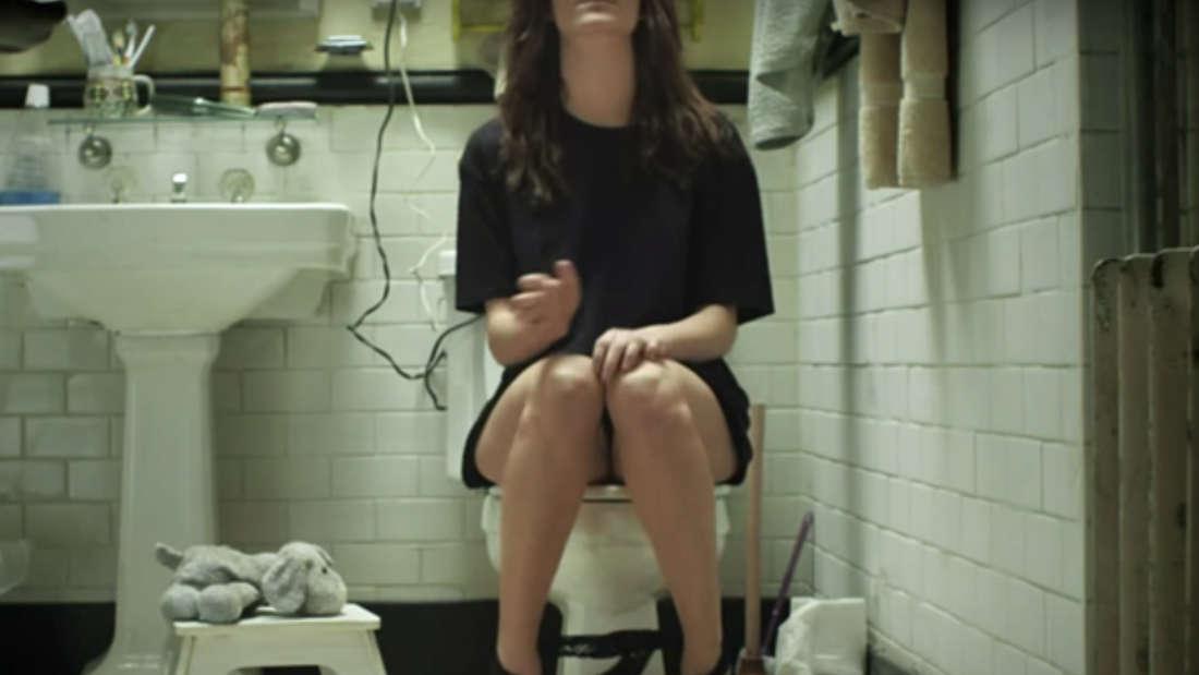 Eine junge Frau sitzt auf der Toilette.