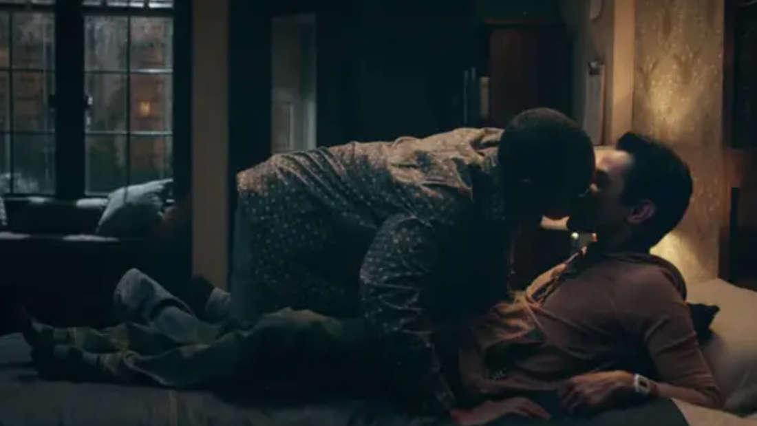 Zwei Männer liegen auf einem Bett und küssen sich.
