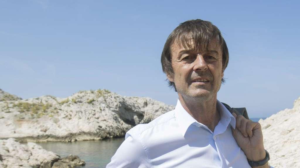 Der frühere französische Umweltminister Nicolas Hulot in weißem Hemd und Sakko über der Schulter vor Wasser.