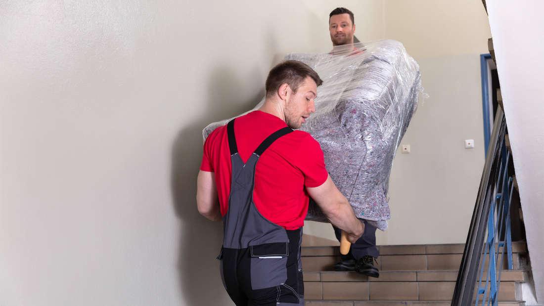 Zwei Männer, die ein Sofa die Treppe hochtragen