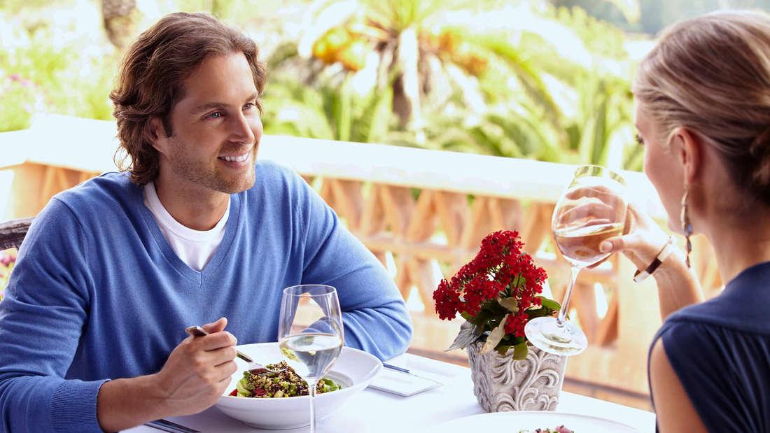 Ein Paar, das gemeinsam am Tisch im Restaurant sitzt und lächelt.