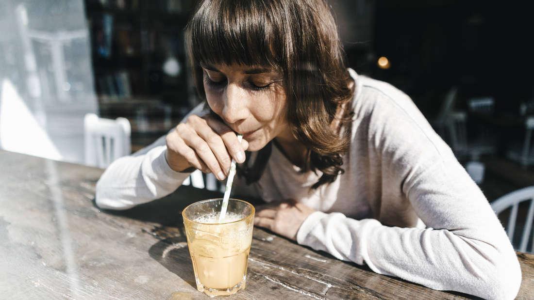 Eine Frau trinkt mit einem Strohhalm aus ihrem Getränk