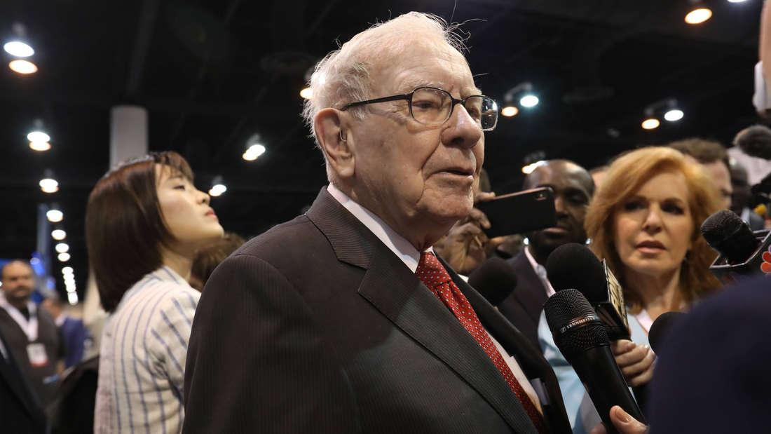 Warren Buffett, der von Reportern interviewt wird.
