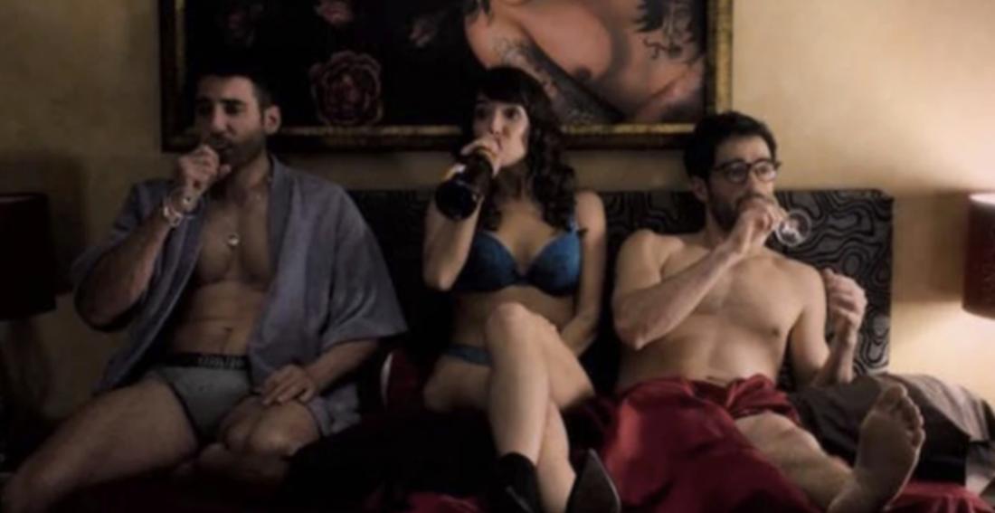 Eine Frau sitzt zwischen zwei Männern auf dem Bett. Alle trinken etwas.