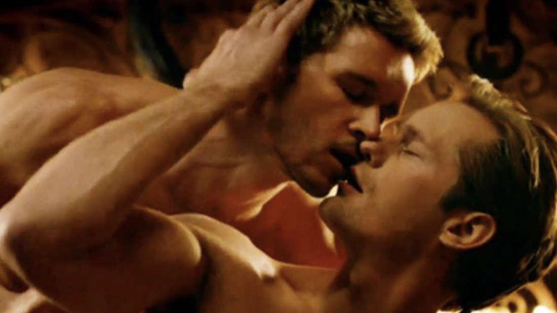Zwei Männer liegen nackt im Bett und küssen sich.
