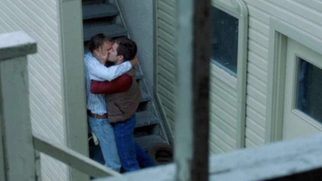 Zwei Männer küssen sich an einem Treppenaufgang.