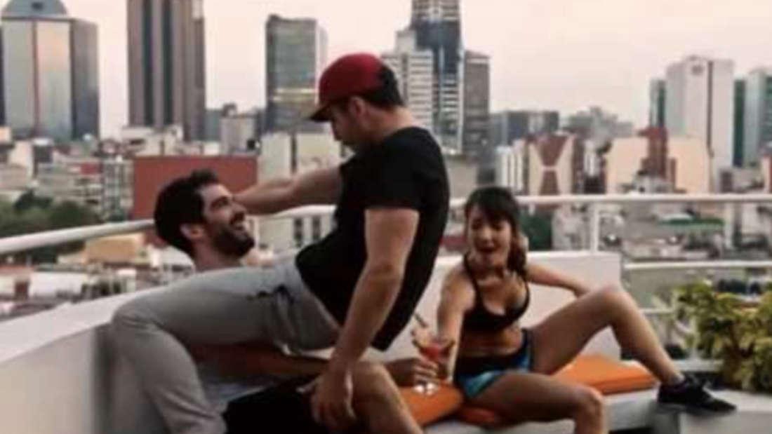 Ein Mann gibt einem anderen einen Lapdance. Beide sind angezogen und haben Spaß.