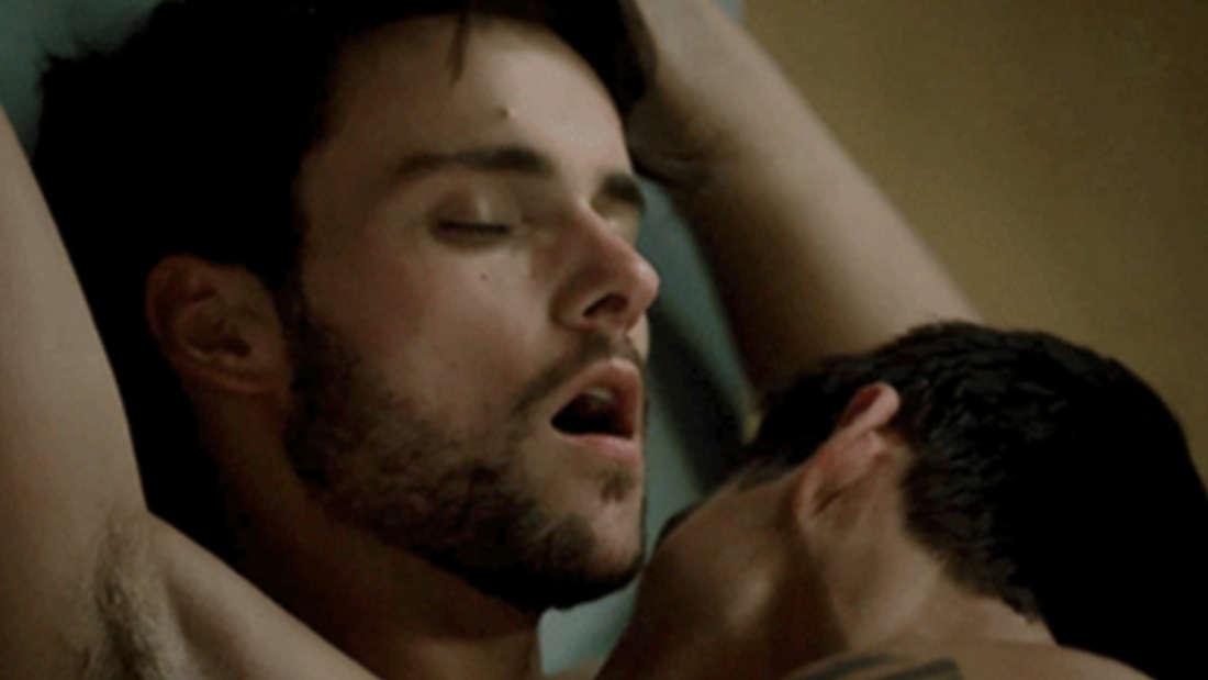 Ein Mann wird von einem anderen auf den Oberkörper geküsst und genießt es sichtlich.