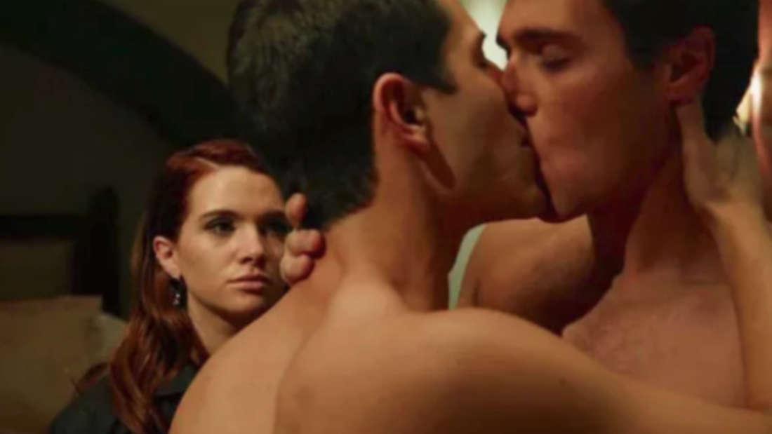 Zwei Männer küssen sich, während eine Frau zusieht.