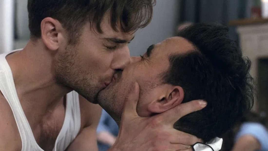 Zwei Männer küssen sich auf die Lippen.