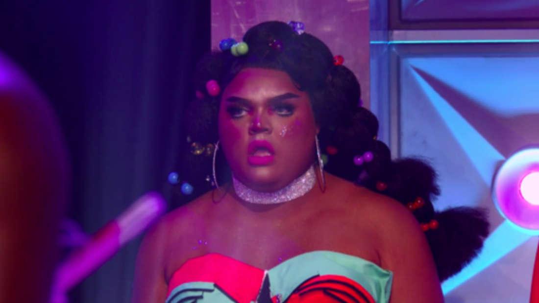 Eine Drag Queen hat ein schockiertes Gesicht aufgesetzt.