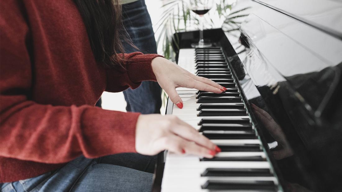 Eine Nahaufnahme mit Fokus auf den Händen von einer Frau, die Klavier spielt