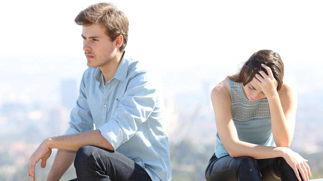 Ein Mann und eine Frau, die beide traurig und enttäuscht aussehen, der Mann hat ihr den Rücken zugekehrt