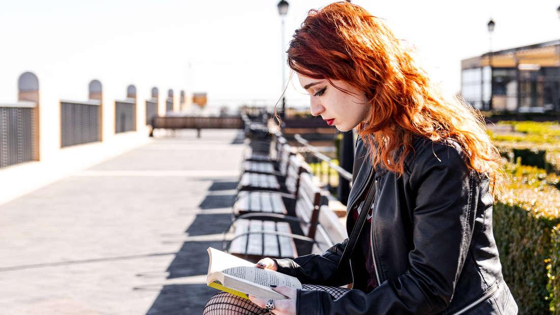 Eine Frau mit roten Haaren, die draußen auf einer Bank ein Buch liest