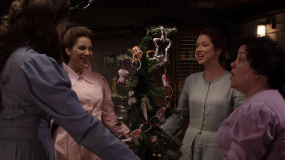Vier Frauen in langen, geschlossenen Kleidern stehen in einem Bunker, um einen Weihnachtsbaum herum.