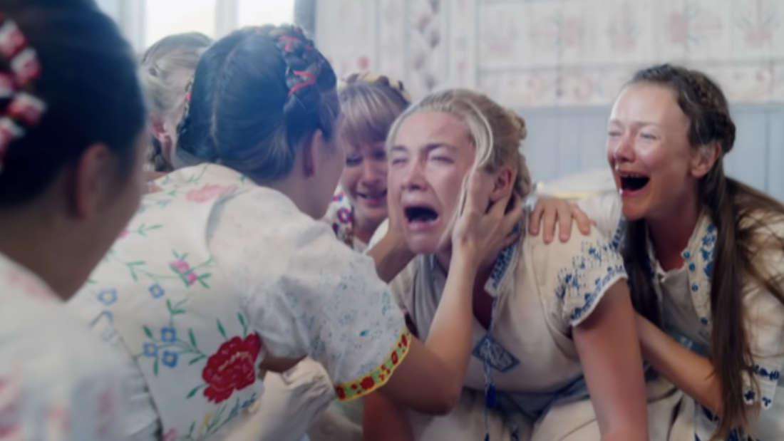 Eine schreiende Frau wird von anderen Frauen umarmt und gehalten.