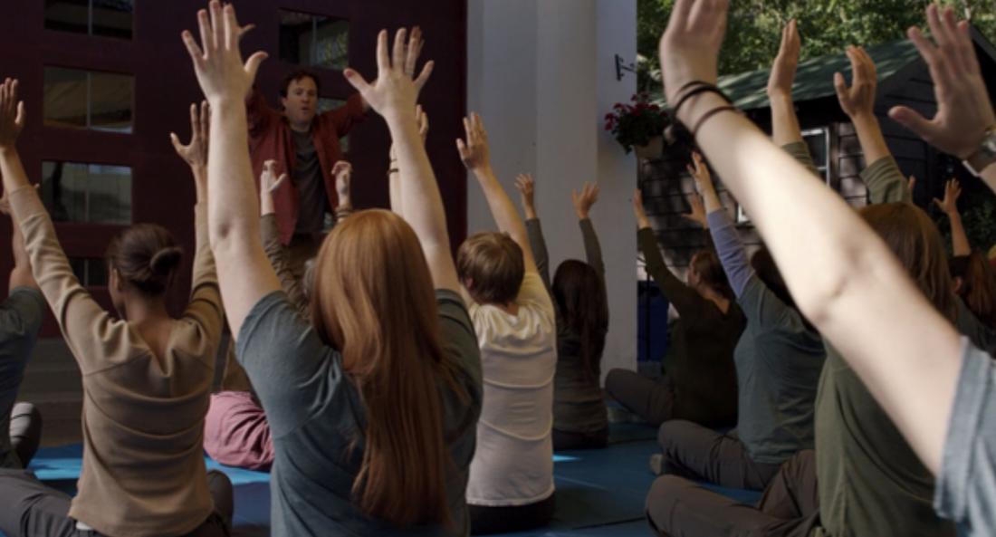 Eine Gruppe sitzender Menschen streckt die Arme nach oben