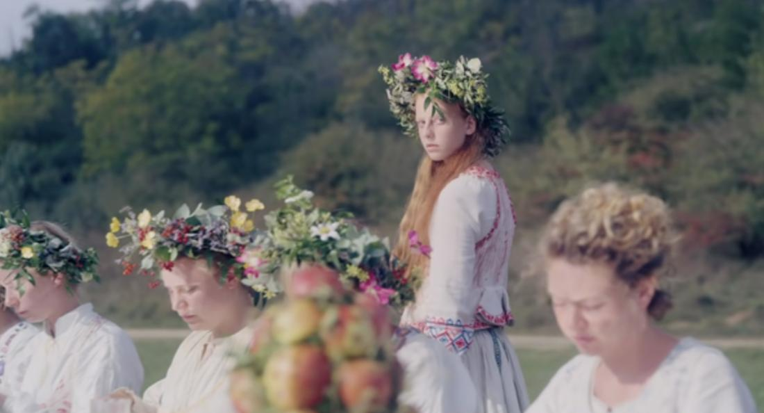 Eine junge Frau in skandinavischer Tracht und Blumenkranz im Haar geht an ähnlich gekleideten Frauen vorbei.