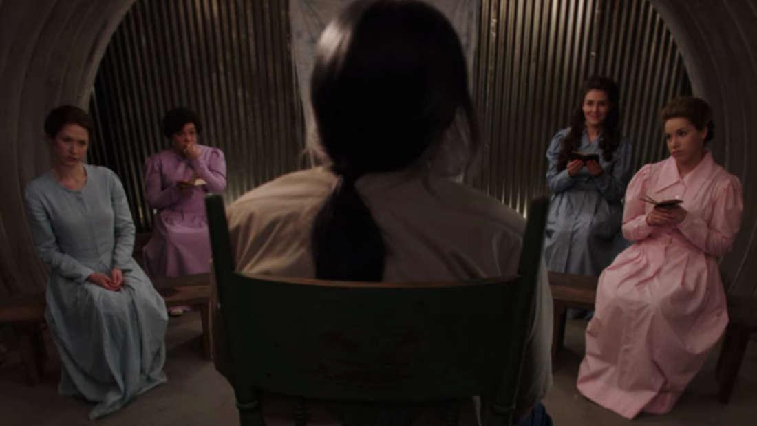 Einige Frauen sitzen in einem Stuhlkreis um einen Mann herum, der nur von hinten zu sehen ist.