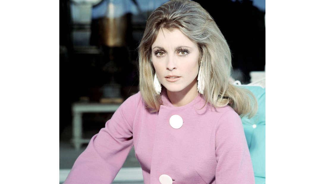 Portraitfoto von Sharon Tate in einem pinken Mantel.