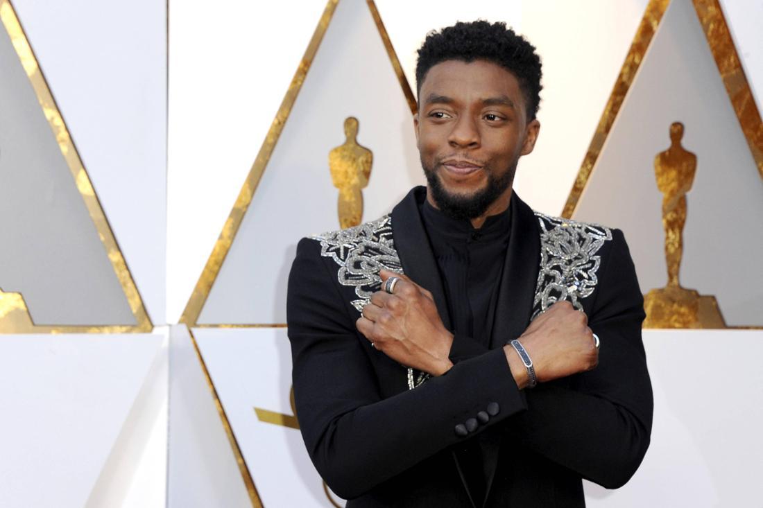 """Chadwick Boseman macht die """"Wakanda Forever""""-Pose auf dem roten Teppich."""