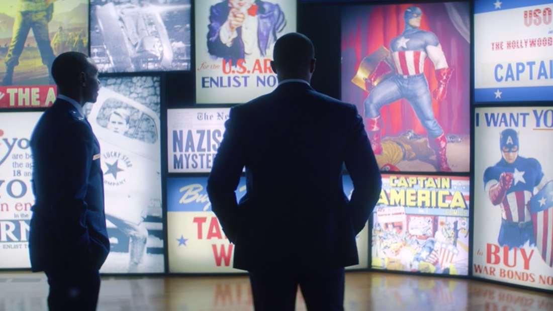 Sam Wilson und James Rhodes stehen vor einer Wand aus alten Captain America Werbungen.