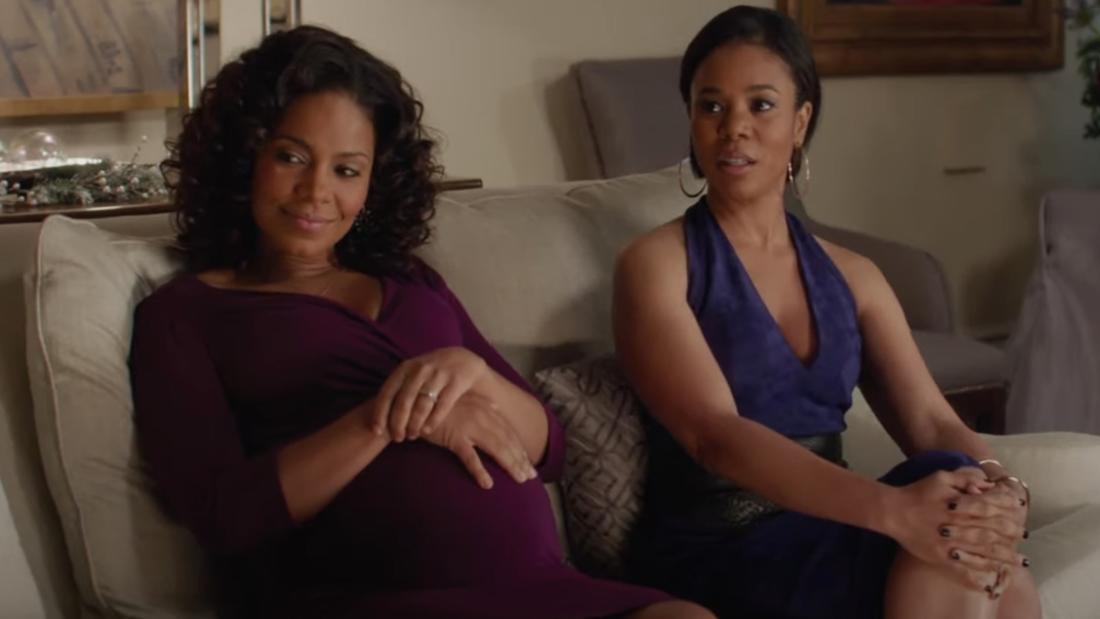 Zwei Frauen, die zusammen auf dem Sofa sitzen. Eine hält die Hände auf ihrem Schwangerschaftsbauch.