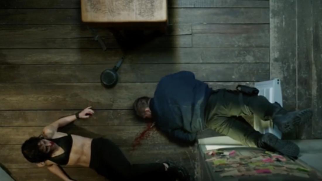 Eine Frau, die neben einem Mann liegt, der bewusstlos geschlagen wurde. Auf dem Boden ist Blut zu sehen.