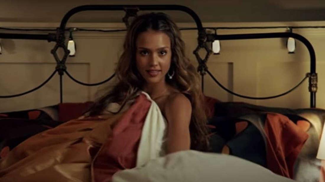 Eine Frau, die im Bett liegt und sich mit der Decke verdeckt