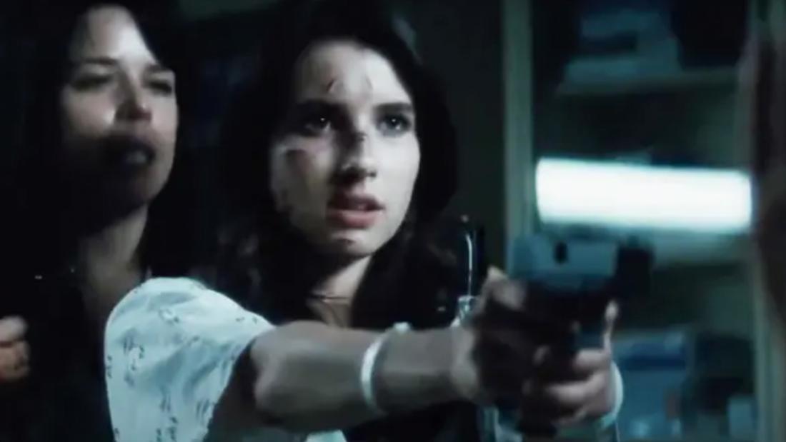 Jemand, der hinter einer Frau steht, die eine Waffe hält.